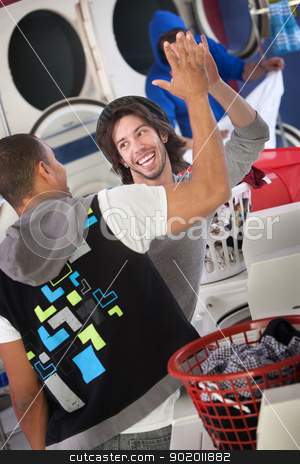 Friends at the Laundromat stock photo, Happy young man gives high five to his friend in a Laundromat by Scott Griessel