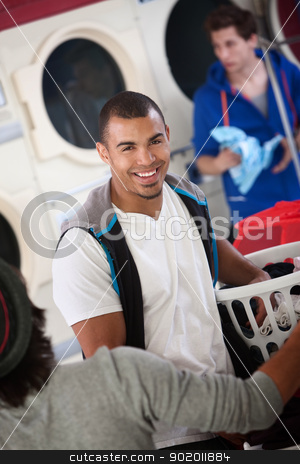 Smiling Young Man stock photo, Young muscular Latino man smiles in laundromat by Scott Griessel