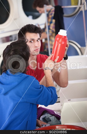 Confused Guys In Laundromat stock photo, Two confused young men in laundromat read the instructions on detergent or conditioner canister by Scott Griessel
