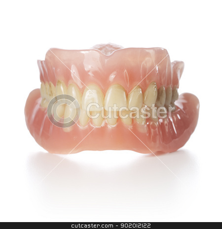 Old Dentures stock photo, Old dentures with yellowed teeth isolated on white with reflection. by Stocksnapper
