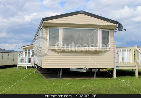Caravan in trailer park stock photo, Scenic view of caravans in trailer park with blue sky and cloudscape background. by Martin Crowdy