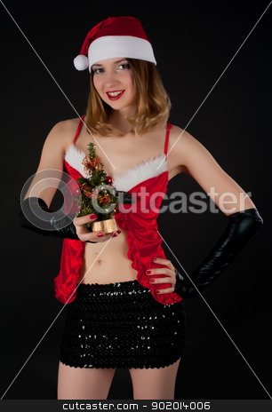 Sexy Santa girl stock photo, Attractive young woman with New Year tree in Santa costume at black background by Aikon