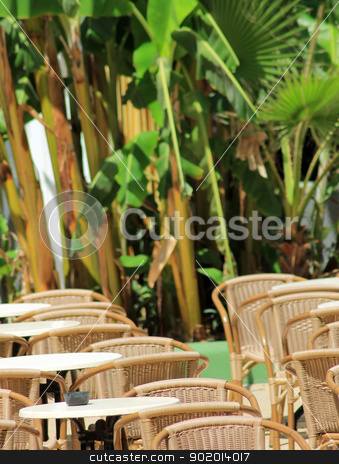 Outdoor restaurant tables stock photo, Outdoor restaurant tables with leafy green palms in background. by Martin Crowdy