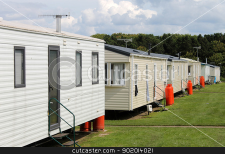 Row of caravan trailers in holiday park stock photo, Row of caravan trailers in holiday park with cloudscape background. by Martin Crowdy