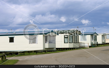Row of caravan trailers stock photo, Row of caravan trailersin holiday park with cloudscape background. by Martin Crowdy