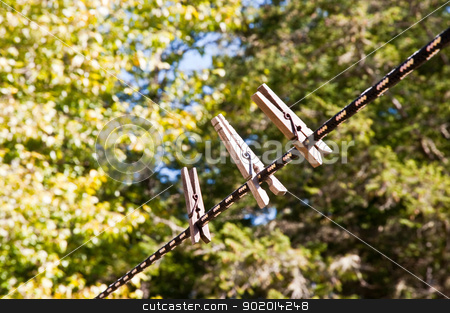 Clothespins stock photo, Clothespins on a line in a yard by Jaime Pharr