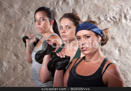Ladies Lifting Weights in Boot Camp Workout stock photo, Three pretty white women working out with kettlebell weights by Scott Griessel