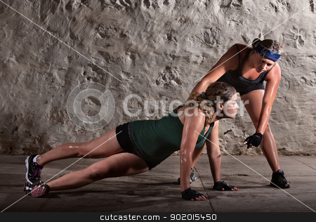 Push-ups During Boot Camp Workout stock photo, Boot camp training instructor helping lady with push-ups by Scott Griessel