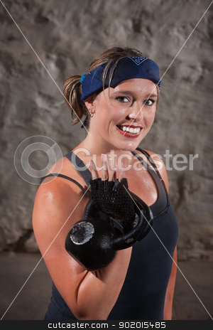 Happy Woman Working Out stock photo, Smiling young woman sweating and lifting a kettle bell weights by Scott Griessel