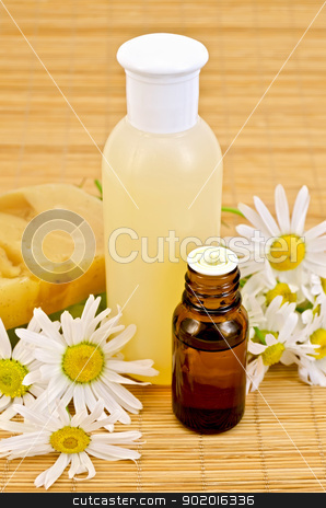 Oil and soap with chamomile stock photo, Oil in a bottle, lotion in a plastic bottle, two homemade soaps, chamomile flowers on a bamboo mat by rezkrr