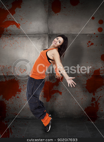 Dancing stock photo, Happy woman dancing over a gray wall by ikostudio