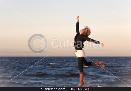 Happy girl stock photo, Happy young woman jumping on the shore of sea by Yulia Chupina