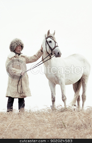 Man and horse stock photo, Man wearing papakhi and his horse - Tersk stallion by Yulia Chupina