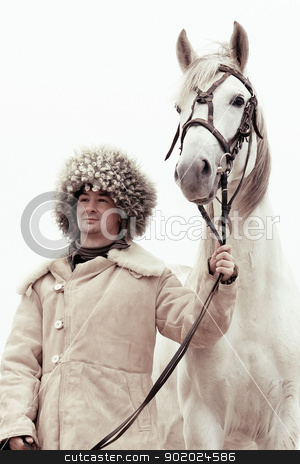 Man and horse stock photo, Man wearing papakhi and his horse - Tersk stallion by Yulia Chupina