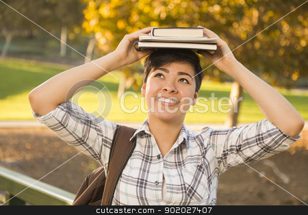 Mixed Race Female Student Holding Books on Her Head stock photo, Portrait of a Pretty Mixed Race Young Female Holding Books on Her Head Outdoors at the Park on a Sunny Afternoon. by Andy Dean