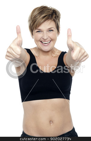 Excited attractive fit lady showing double thumbs up stock photo, Attractive fit lady in workout wear showing double thumbs up to camera by Ishay Botbol