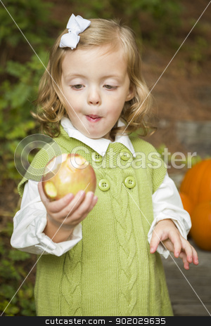 Adorable Child Girl Eating Red Apple Outside stock photo, Adorable Child Gilr Eating a Delicious Red Apple Outside. by Andy Dean