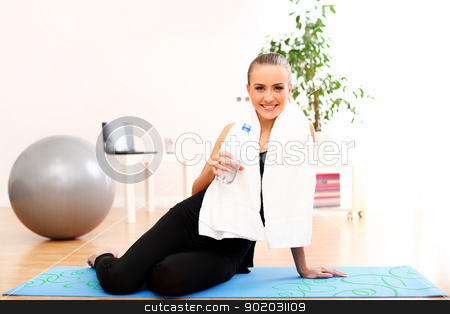 Girl with towel drink water after fitness training stock photo, Closeup of girl with towel drinking water after fitness training at home by yekostock