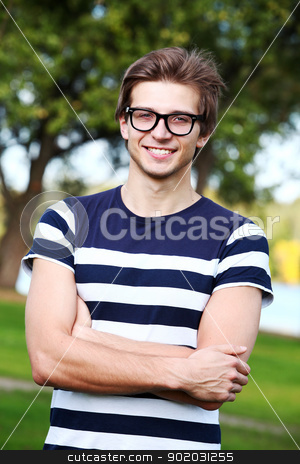 Portrait of young cute man with glasses in park stock photo, Portrait of young and smiling cute man with glasses in park by yekostock