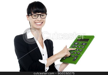 Bespectacled woman using big green calculator stock photo, Bespectacled smiling woman using big green calculator, pressing key 5 by Ishay Botbol