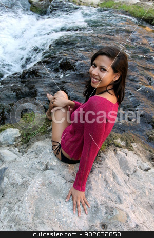 Young Hispanic Woman At Creek stock photo, Hispanic woman sitting at water edge of a creek. by Henrik Lehnerer