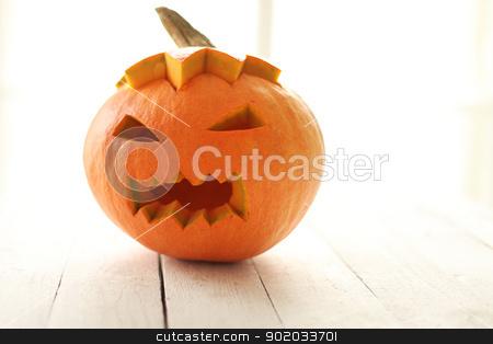 Halloween pumpkin stock photo, Halloween pumpkin on a white wooden surface by yekostock