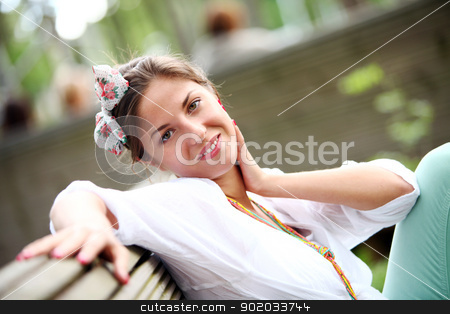 A beautiful woman is sitting on a park bench stock photo, A beautiful woman is sitting on a park bench on a blurred background by yekostock