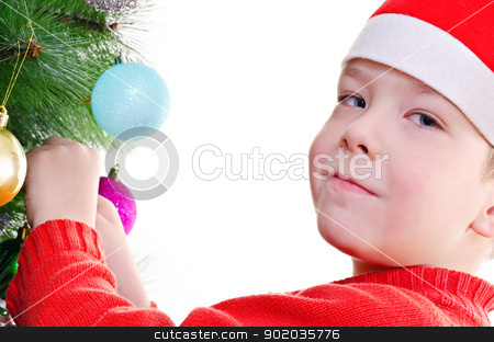 Christmas decoration stock photo, Young boy decorating christmas tree, looking at camera, horizontal shot by Milsi Art