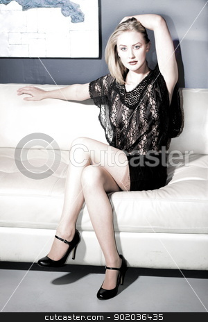 Woman On Couch stock photo, Beautiful blond woman sitting on a couch. by Henrik Lehnerer