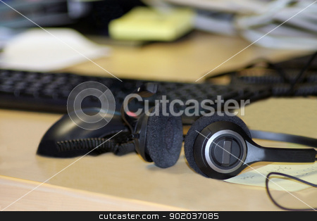 Headset on office desk stock photo, Headset on computer desk with keyboard in background. by Martin Crowdy