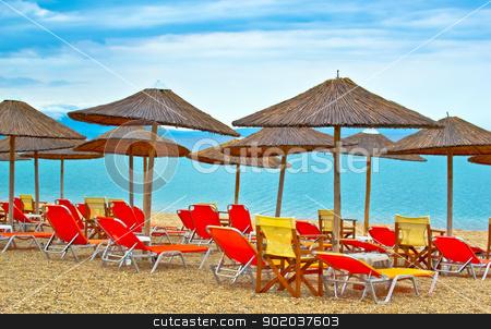 Sun loungers with an umbrella on the beach with cloudy sky stock photo, Sun loungers with an umbrella on the beach with cloudy sky by vician