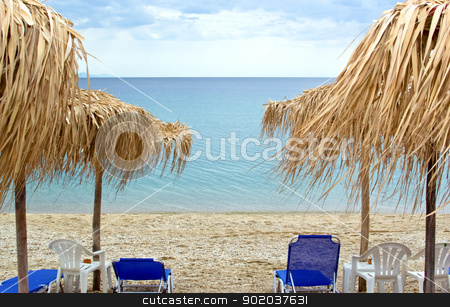 Sun loungers with an umbrella on the beach with cloudy sky stock photo, Sun loungers with an umbrella on the beach with cloudy sky by vician