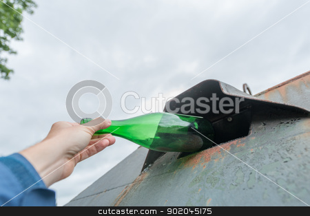 Glass waste stock photo, Person throwing a green bottle in a container  by Picturehunter