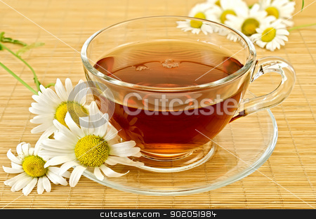 Herbal tea with camomiles on a bamboo stock photo, Herbal tea in a glass cup and saucer, camomiles on a background of bamboo napkins by rezkrr