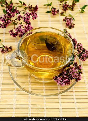 Herbal tea with oregano on bamboo stock photo, Herbal tea in a glass cup and saucer, oregano sprigs of flowers on a background of bamboo napkins by rezkrr