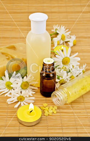 Oil with yellow soap and salt stock photo, Oil in a bottle, the lotion in a plastic bottle, two homemade soaps, bath salts, two candles with flames and chamomile flowers on a bamboo mat by rezkrr