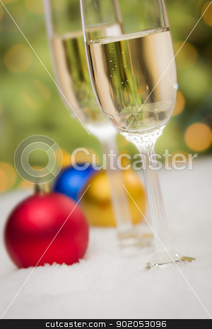 Christmas Ornaments and Champagne Glasses on Snow stock photo, Beautiful Various Colored Christmas Ornaments and Champagne Glasses on Snow Flakes In Front of an Abstract Background. by Andy Dean