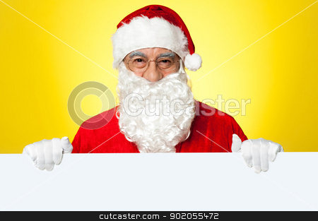 Male Santa standing behind big blank banner ad board stock photo, Male Santa standing behind big blank banner ad board. Business concept by Ishay Botbol