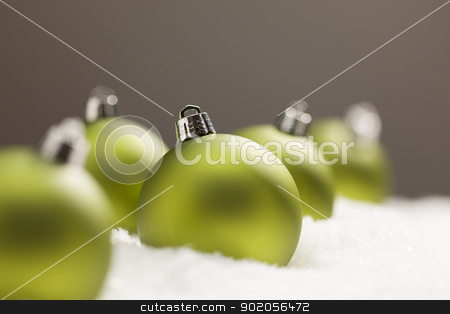 Green Christmas Ornaments on Snow Over a Grey Background stock photo, Green Christmas Ornaments on Snow Flakes Over a Grey Background by Andy Dean