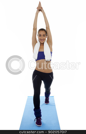 Fit woman doing stretching exercise stock photo, Fit woman doing stretching exercise on blue mat. Full length studio shot. by Ishay Botbol