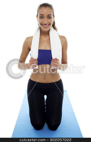 Woman in gym wear kneeling on blue mat stock photo, Woman in gym wear kneeling on blue mat. Ready to start her workout. by Ishay Botbol