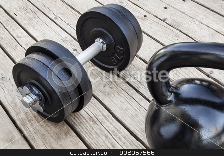 kettlebell and dumbbell stock photo, exercise weights - kettlebell and dumbbells on a wooden deck - a home gym concept by Marek Uliasz