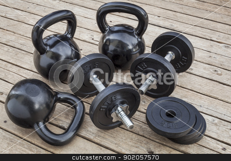 kettlebells and dumbbells stock photo, exercise weights - kettlebells and dumbbells on a wooden deck - a home gym concept by Marek Uliasz
