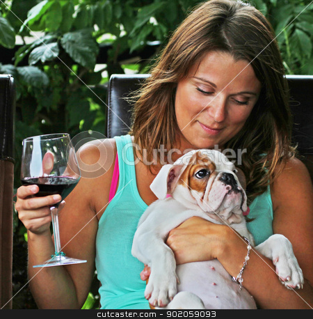 woman with bulldog stock photo, Alyssa with Daisy and a glass of wine on the deck in summer. by Gord Springford