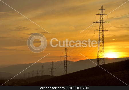 Electricity pylons in the dusk stock photo, A line of electricity pylons disappearing into the distance at sunset by Alistair Scott