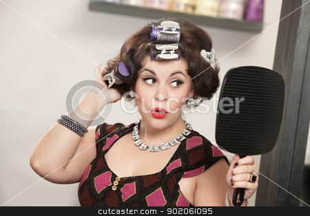 Happy Woman Looking in Mirror stock photo, Proud woman in curlers looking in a mirror by Scott Griessel