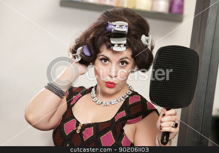 Woman in Curlers Holding Mirror stock photo, Impressed woman in curlers holding a mirror by Scott Griessel