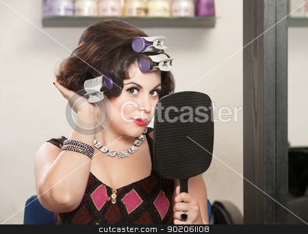 Lady Feeling New Hairdo stock photo, Caucasian woman in curlers with mirror feeling her hair by Scott Griessel