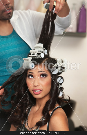 Young Woman Watches Curler Removal stock photo, Pretty young woman watching curlers being removed from hair by Scott Griessel