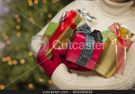 Woman Wearing Seasonal Red Mittens Holding Christmas Gifts stock photo, Woman Wearing A Sweater and Seasonal Red Mittens Against an Abstract Green and Golden Background Holding Beautifully Wrapped Christmas Gifts. by Andy Dean